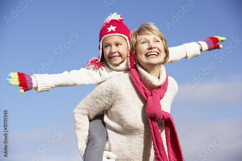 Grandmother Giving Her Granddaughter A Piggy Back Ride