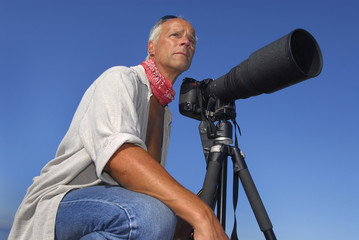 Handsome mature man adventurer posing with a big camera outdoors