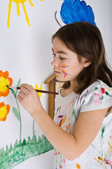 Young girl painting on wall