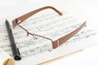 glasses, ball pen and old musical notes on white background