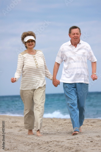 Romantic mature couple jogging  at the beach