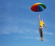 Flying girl with colorful umbrella in the blue blue sky