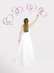 Bride drawing hearts on the wall