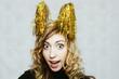 Leinwanddruck Bild - blonde crazy girl with party golden tinsel horns