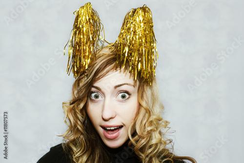 Leinwanddruck Bild blonde crazy girl with party golden tinsel horns