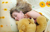 Young girl asleep in her bed with a teddy bear poster