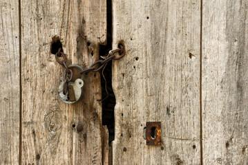 verrostete Kette mit Vorhängeschloss an maroder Holztür