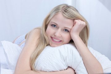 Cute smiling girl on pillow in bedroom