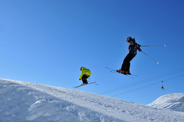 Two skiers jumping together