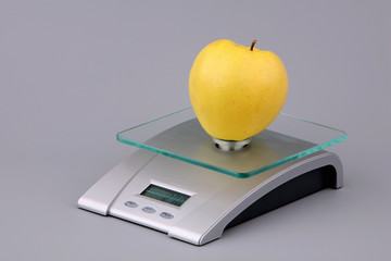 Yellow apple on scales