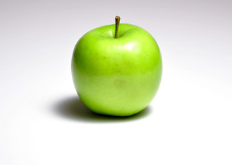 Green apple on a white background with a heavy shadow