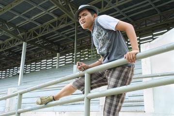 Asian man on fence of sports stadium