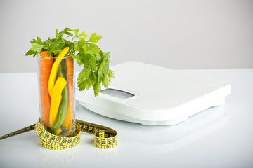 healthy vegetables in a glass surrounded by a measuring tape