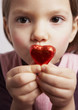 child presenting red candy heart