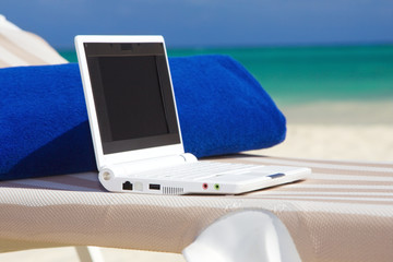 laptop and towel on the beach chaise longue