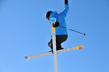 skier in blue jacket doing a helicopter jump
