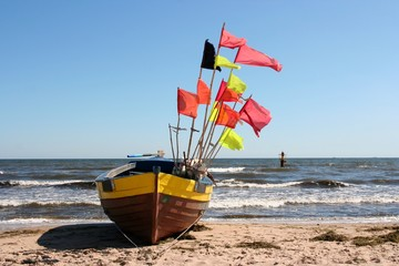 Old fishing boat with flags on shore line