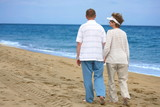Romantic mature couple walking at the beach