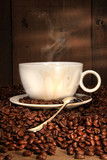 Fototapety White coffee cup with spoon on roasted beans