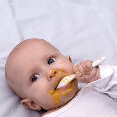 Baby isst Brei mit Löffel