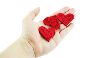 Men's hand holding three hearts