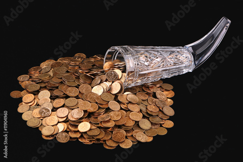 Crystal glass and small coins on a black background