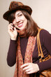 The girl in a felt hat and an orange scarf speaks by phone.
