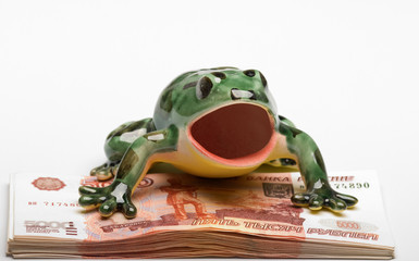 Ceramic frog on a pile of five-thousandth denominations
