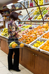 Woman shopping for fruits at grocery store