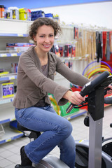 Young  woman on sports training apparatus in shop