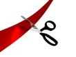 Scissors cutting a red ribbon