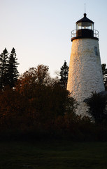 Nice sunset scene aged  rock lighthouse in Castine, Maine.