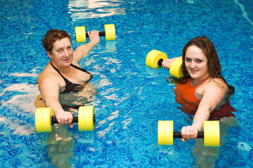 two womam in water with dumbbells
