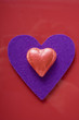 red heart-shaped chocolate on purple felt heart