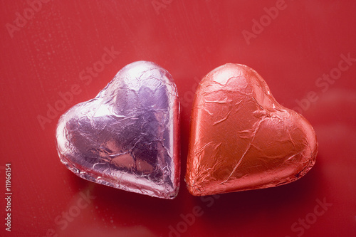 two heart-shaped chocolates in foil
