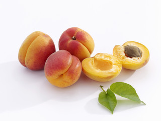 a few apricots with leaves, whole and halved