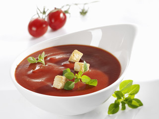 tomato sauce with croutons and basil in white dish
