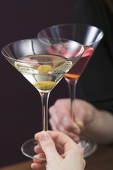 hands clinking glass of martini & glass of cosmopolitan