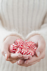 hands holding red and white striped peppermints