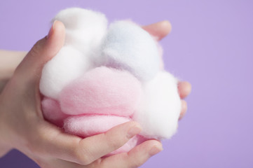 hands holding cotton wool balls