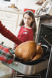woman taking turkey out of oven, girl in background