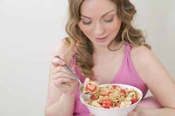 woman eating cornflakes with strawberries