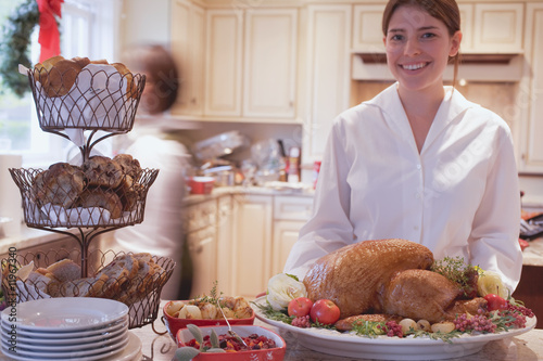 young woman in kitchen with roast turkey for christmas