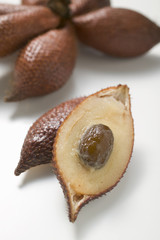 several salak fruits, whole and halved