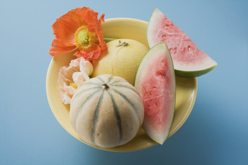 three different melons in bowl (overhead view)