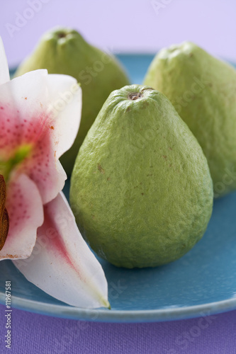 three guavas on plate with orchid