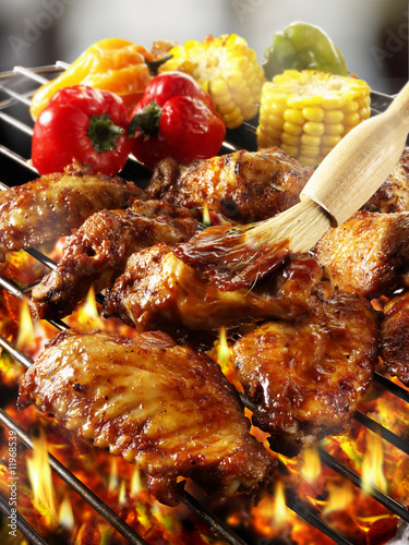 brushing chicken wings on barbecue rack with marinade
