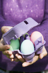 woman holding egg box full of coloured eggs