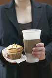 woman holding muffin and plastic coffee cup