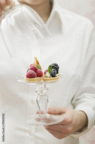 woman serving assorted berry tarts